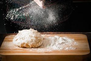 Chefkoch knetet Pizzateig auf einem Brett foto
