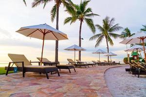 Sonnenschirm und Stuhl um den Pool im Hotelresort mit Sonnenaufgang am Morgen? foto