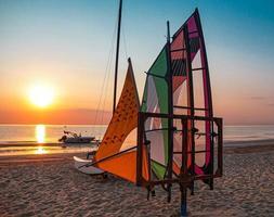 Mehrfarbige Windsurfsegel und Motorboot am leeren Strand im Morgengrauen während des wunderschönen Sonnenaufgangs am Meer in Rivazzurra Rimini, Italien, Adriaküste foto