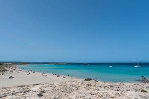 Menschen an der Küste von Ses Illetes Strand auf Formentera, Balearen in Spanien. foto