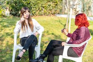 Mädchen rauchen elektronische Zigarette im Garten foto