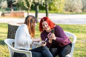 Freundinnen mit Smartphone und Zigarette rauchen foto