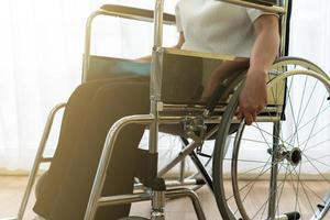 asiatische junge behinderte frau mit glücklichem und hoffnungsvollem gefühl, die allein im haus auf dem rollstuhl sitzt. Handicap- und Behinderungskonzept foto