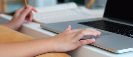 ein junges asiatisches mädchen, das während der covid-19- oder Coronavirus-Pandemie einen Computer verwendet, um zu Hause als Protokoll zur sozialen Distanzierung zu lernen. Homeschooling-Konzept foto
