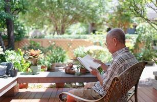 Senior asiatischer pensionierter Mann sitzt auf der Bank und liest in der Freizeit ein Buch zu Hause im Hinterhof foto
