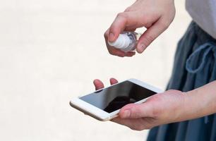 Frau besprüht Telefon mit Desinfektionsmittel foto