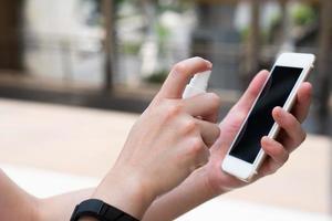 Frau, die den Bildschirm des Smartphones reinigt foto