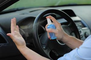 Mann reinigt die Hände vor der Reise mit antibakteriellem Spray foto