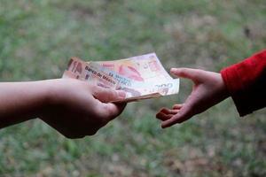 Hand einer Frau, die einem Minderjährigen in einem Garten mexikanisches Geld überreicht foto