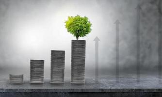 Wachsendes Geschäftswachstum und finanzieller Anbau von Pflanzen aus Münzen in Glasflaschen auf grünem Hintergrund foto