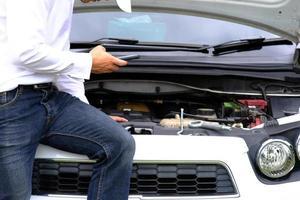 asiatischer junger Mann, der auf einem kaputten Auto sitzt und um Hilfe bittet und Radfahrzeuge auf der Straße repariert, Winter- und Sommerreifen ersetzt. saisonales Reifenwechselkonzept foto