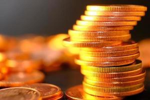 Schließen Sie goldene Münzen auf Tischhintergrund und sparen Sie Geld und Geschäftswachstumskonzept, Finanz- und Investitionskonzept foto