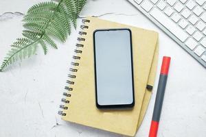 Smartphone mit leerem Bildschirm auf dem Notizblock auf dem Tisch foto