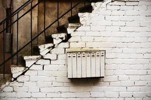 weißer Briefkasten mit mehreren Abteilungen, der an einer weißen Mauer unter der Treppe hängt foto