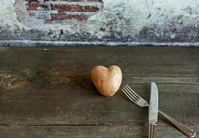rote Kartoffel in Herzform auf Holzuntergrund mit Gabel und Messer with foto