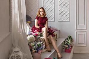 Ein süßes, stilvolles junges Mädchen in einem eleganten burgunderroten Kleid sitzt am Fenster foto