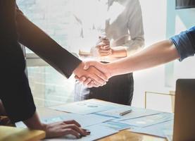 Zwei Geschäftsleute geben sich nach Abschluss einer endgültigen Projektvereinbarung die Hand, um das Geschäft zwischen den beiden Unternehmen zu stärken foto
