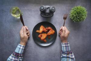 Mans Hände mit Messer und Gabel warten darauf, gebratene Hähnchenfilets auf dem Teller zu essen foto