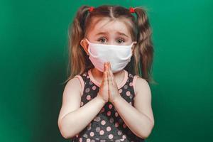 Kaukasisches krankes kleines Mädchen in medizinischer Maske während der Coronavirus-Epidemie betet auf grünem Hintergrund, Nahaufnahme foto