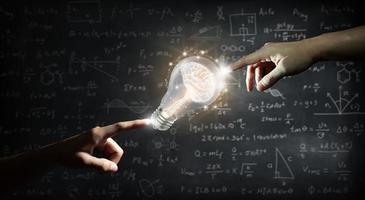 Hand zeigt auf ein Gehirn in einer Glühbirne an der Wandtafel foto