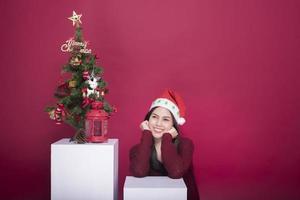 schönes Weihnachtsmann-Mädchen im Studio auf rotem Hintergrund, Weihnachtskonzept foto