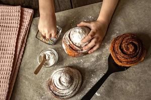Kinderhände im Rahmen bestreut ein frisch gebackenes Brötchen mit Zimt foto