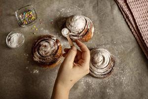 Frauenhand streut Puderzucker auf frisch gebackene Zimtschnecken foto