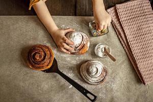 Kinderhände im Rahmen, die ein frisch gebackenes Brötchen mit Streuseln bestreuen foto