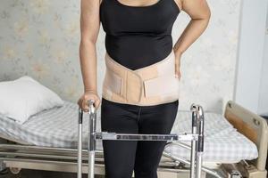 asiatische Patientin mit Rückenschmerzen-Unterstützungsgurt für orthopädische Lendenwirbelsäule mit Gehhilfe. foto