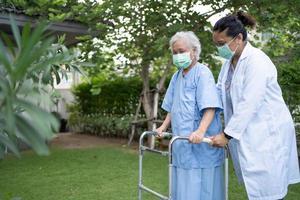 Arzt Hilfe und Pflege asiatische Senioren oder ältere alte Damen verwenden Walker mit starker Gesundheit, während sie im Park in einem glücklichen, frischen Urlaub spazieren gehen. foto