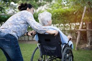 Arzt hilft und pflegt asiatische Senioren oder ältere Frauen, die auf Rollstuhl im Park in der Krankenstation sitzen, gesundes, starkes medizinisches Konzept. foto