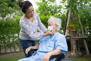 Helfen Sie asiatischen Senioren oder älteren alten Damen im Rollstuhl und tragen Sie eine Gesichtsmaske zum Schutz der Sicherheitsinfektion Covid-19 Coronavirus im Park. foto