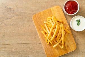 Pommes Frites mit Sauerrahm und Ketchup foto