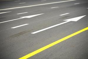 Asphaltstraße mit Linien und Pfeilen foto