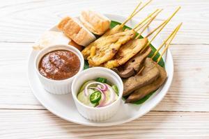 Schweinefleisch-Satay mit Erdnusssauce und Gurken, Gurkenscheiben und Zwiebeln in Essig foto