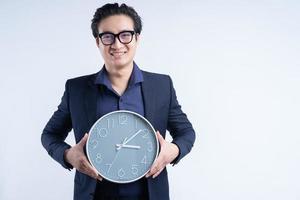 Porträt des asiatischen Geschäftsmannes, der Uhr hält foto