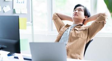 asiatischer Geschäftsmann, der sich beim Arbeiten entspannt foto