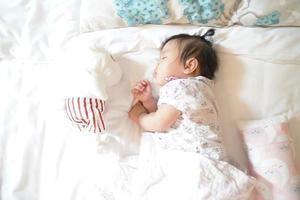 süßes, verschlafenes 1-jähriges asiatisches Säuglingsmädchen, das auf weicher Bettwäsche mit einer Puppe schläft, neugeborenes Konzept. foto