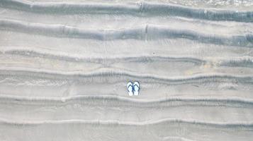 Flip-Flops am Sandstrand, Sommerferienhintergrund, Luftdraufsicht foto