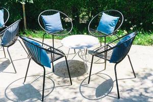 Terrasse mit Kissen auf Stuhl und Tischgarnitur foto