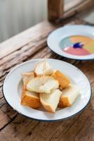 gedämpftes Toastbrot mit buntem Vanillepudding auf Holzhintergrund foto