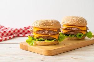 Schweine-Hamburger oder Schweine-Burger mit Käse auf Holzbrett foto