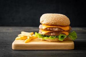 Schweinefleisch-Hamburger oder Schweinefleisch-Burger mit Käse und Pommes frites foto