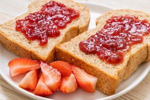 hausgemachtes Vollkornbrot mit Erdbeermarmelade und frischen Erdbeeren foto