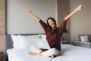 Portrait schöne junge asiatische Frauen mit Computer und Handy auf dem Bett foto