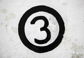 Nummer drei an einer weißen Wand foto