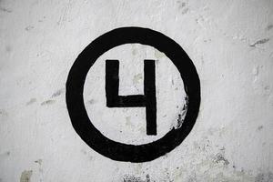 Nummer vier an einer weißen Wand foto