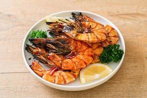 gegrillte Tigergarnelen oder Shrimps mit Zitrone auf einem Teller foto