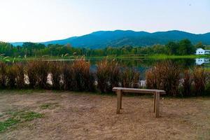 Holzbank mit einem wunderschönen See in Chiang Mai mit bewaldeten Bergen und Dämmerungshimmel in Thailand foto