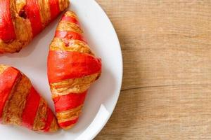 frisches Croissant mit Erdbeermarmeladesauce auf Teller foto